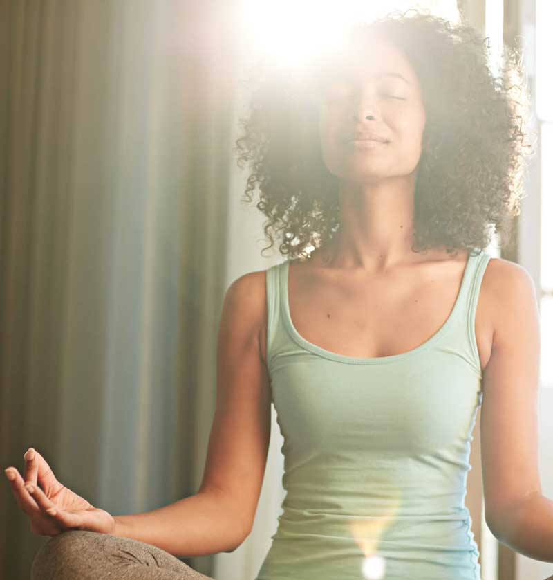 A woman in pajamas meditates with the sun shining