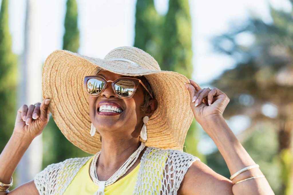 A smiling woman in a sun hat and sunglasses