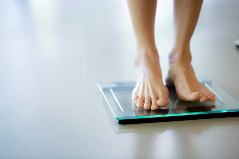 a woman stands on a modern glass scale barefoot